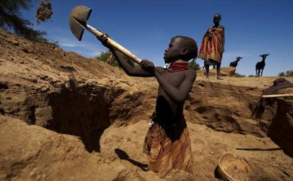 Uma menina cava à procura de água no leito seco de um rio