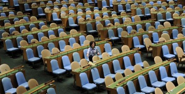 Mulher espana os cadeiras do plenário da assembleia geral da ONU, em Nova Iorque, onde em poucas horas os líderes de cem países estarão reunidos. Foto de Justin Lane/EP