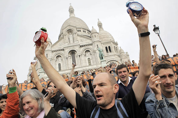 Ativistas ambientais e de direitos humanos levantam simbolicamente os despertadores em frente à Sacre Coeur, em Paris, durante o evento que pretendeu acordar os líderes mundiais para a conferência do clima em Copenhague. Foto de Thibault Camus/AP