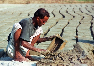 Homem molda os tijolos em uma fábrica tradicional de Bangladesh